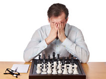 Man covered face with his hands in heavy chess game Stock Photos