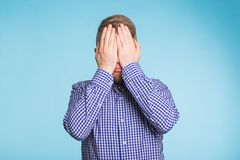 Man covered his face with hand on blue background Stock Photo