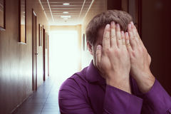 Man covered his face with hands. Man covers his face with hands standing in the corridor stock photography