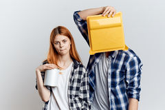 Man covered his face with plastic paint bath woman holding paint cans royalty free stock photography
