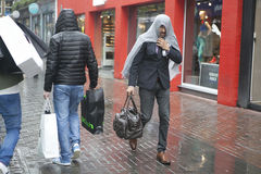 The man covered his head by jacket in heavy rain. Royalty Free Stock Images