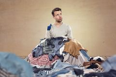 Man covered by laundry. A man is covered by a heap of laundry. He is looking upwards to the right as if thinking of what to do next Royalty Free Stock Photos