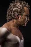 Man covered in mud, naked, in profile Stock Photo