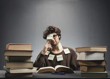 Man covered in sticky notes, studying. Stock Images