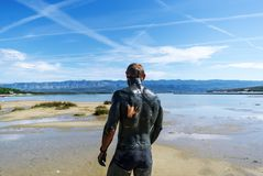 The man covered with therapeutic mud walks on the beach. The mud of Adriatic sea is being used with the therapy purposses for the people with skin problems royalty free stock photos