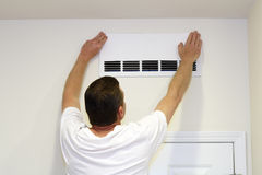 Man Covering Air Vent. Male placing a paper cover over part of an air return intake vent to increase air return in another vent in the home stock image
