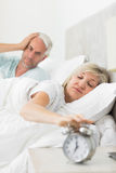 Man covering ears while woman extending hand to alarm clock in bed Stock Images
