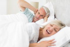Man covering ears while woman shouting in bed Stock Image