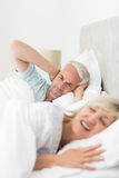 Man covering ears while woman shouting in bed Stock Photo