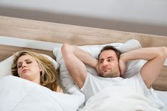 Man covering ears while woman sleeping Stock Photography