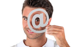 Man covering eye with at symbol Stock Photo