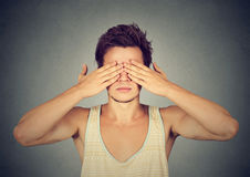Man covering eyes with hands cant see, hiding. On gray background Royalty Free Stock Images