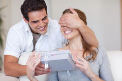 Man covering the eyes of his girlfriend while giving her a prese Royalty Free Stock Image