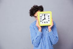 Man covering face with clock and looking at camera Royalty Free Stock Photos