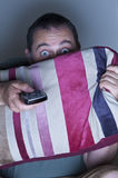 Man covering face with a cushion watching tv Royalty Free Stock Images