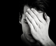 Man covering face with hand Stock Images