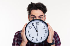 Man covering her face with wall clock Stock Images