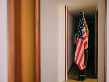 Man covering himself with the United States flag stock photography