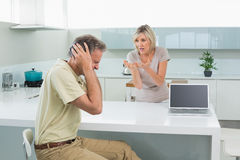 Man covering his ears as woman argue in kitchen Stock Image