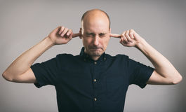 Man covering his ears. Bald man covering his ears over gray background Royalty Free Stock Image