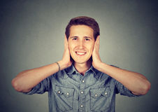 Man covering his ears with hands. Hear no evil concept Stock Photo