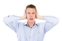 Man covering his ears looking up, headache from loud noise Stock Photo