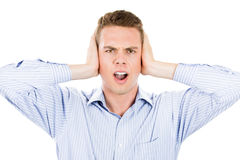 Man covering his ears looking up, headache from loud noise Stock Image