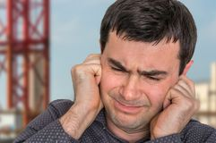 Man covering his ears to protect from loud noise royalty free stock photo