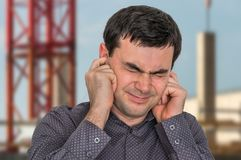 Man covering his ears to protect from loud noise. Excessive sound stock photos