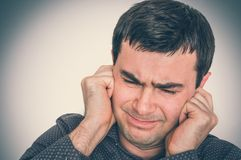 Man covering his ears to protect from loud noise. Excessive sound - retro style stock image