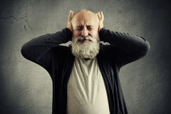 Man covering his ears and wincing Stock Images