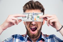 Man covering his eyes with bill of USA dollar Royalty Free Stock Photos