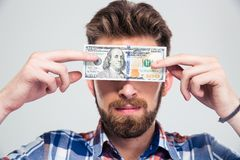 Man covering his eyes with bill of USA dollar Stock Photos