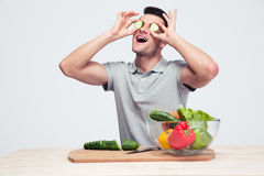 Man covering his eyes with cucumber Royalty Free Stock Image