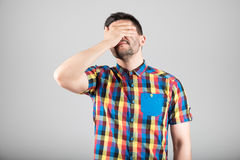 Man covering his eyes stock image