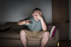 Man covering his eyes watching tv Royalty Free Stock Image
