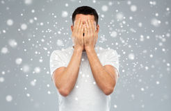 Man covering his face with hands over snow. People, fear, emotions, winter and stress concept - man in white t-shirt covering his face with hands over snow on Royalty Free Stock Photo