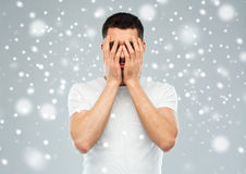 Man covering his face with hands over snow. People, fear, emotions, winter and stress concept - man in white t-shirt covering his face with hands over snow on Stock Photos