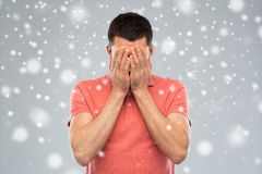 Man covering his face with hands over snow. People, fear, emotions, winter and stress concept - man in white t-shirt covering his face with hands over snow on Royalty Free Stock Photography