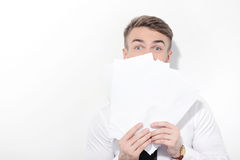Man covering his face with some papers Royalty Free Stock Photo