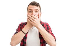 Man Trying Hard To Keep Secrets With Himself. Man covering his mouth in disbelief about some scandal in studio stock photos