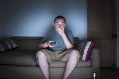 Man covering mouth watching tv Stock Images