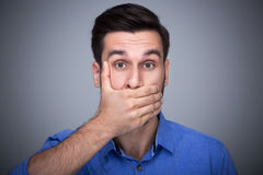 Man covering mouth. Young man over grey background Stock Images