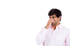 Man covering nose his nose, something stinks, Stock Photo