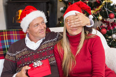 Man covering partner eyes and offering a gift to her Stock Image
