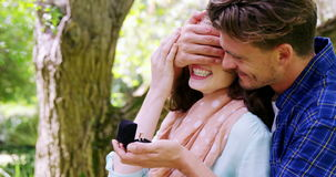 Man covering woman eyes while giving her surprise gift. In park stock footage