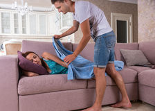 Man Covering Woman Sleeping on Sofa with Blanket Stock Images