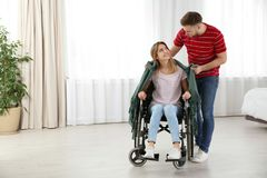 Man covering woman in wheelchair with plaid at home stock photography