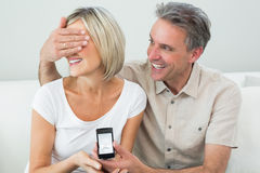 Man covering womans eyes to offer her an engagement ring Royalty Free Stock Images