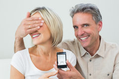 Man covering womans eyes to offer her an engagement ring Stock Image